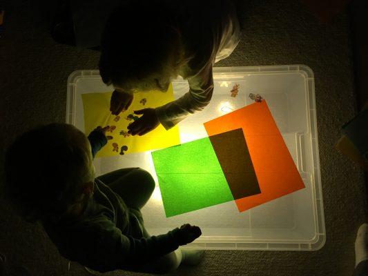 Deti tvoria, experimentujú a hrajú sa s farebnými papiermi na svetelnej podložke